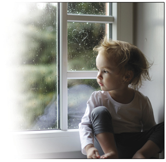 Toddler looking out a window on a rainy day